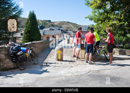 pilgrims with bycicles resting at romanic bridge of Rio Meruelo, Spain, Leon, Kastilien, Molinaseca - Stock Photo