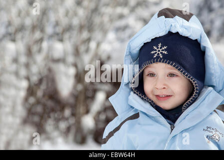 portrait of a little boy standing in a winter landscape with shining eyes - Stock Photo