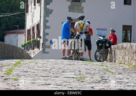 bike pilgrims on a medieval bridge over Rio Ulzama, Spain, Basque country, Navarra, Trinidad de Arre, bask. Villava - Stock Photo