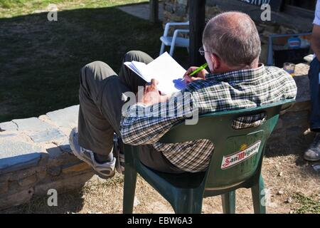 pilgrim doing diary notes, Spain, Kastilien & Le�n, Leon, Foncebad�n - Stock Photo
