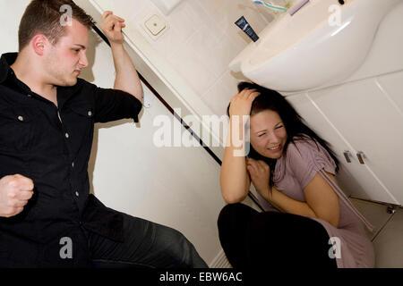 youn man beating young woman in bathroom - Stock Photo