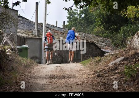 two pilgrims on the Way of St James to Lavandeira, Spain, Galicia, Lugo - Stock Photo
