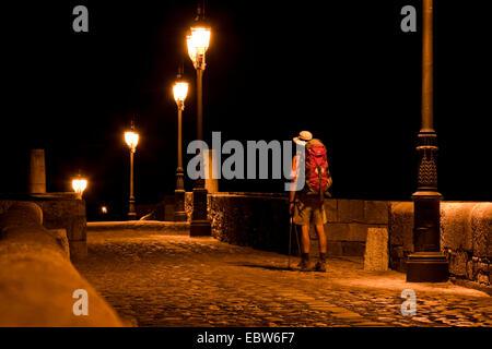 nightly arrival of a pilgrim on the mediaeval bridge 'Puente de �rbigo', Spain, Kastilien und Le�n, Hospital de - Stock Photo