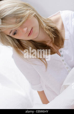 contemplative young blond woman sitting in bed - Stock Photo