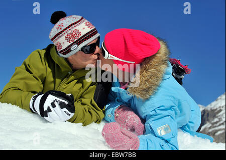 couple on winter vacation lying in the snow side by side on their bellies kissing each other, France - Stock Photo