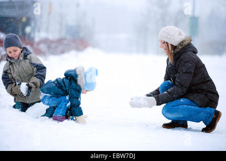 a mother playing with her two little children in snow - Stock Photo