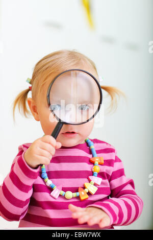a little girl looking through a loupe - Stock Photo