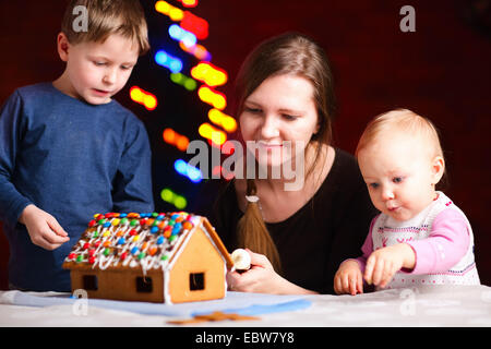 mother is making a gingerbread house with her little children - Stock Photo