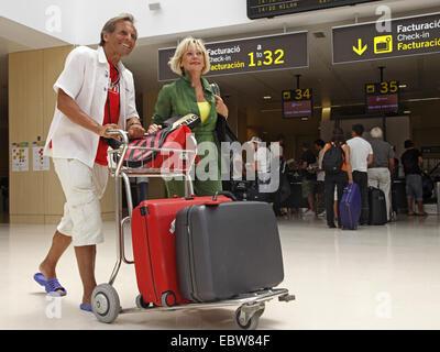 senior couple in arrivals hall - Stock Photo