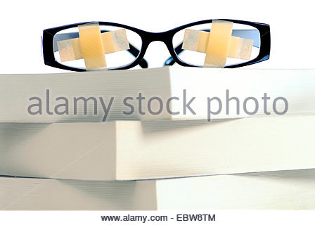 glasses with plasters on a stack of books, symbol picture for education strike, education misery - Stock Photo