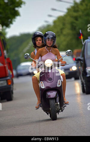two attractive young women riding on motor scooter - Stock Photo