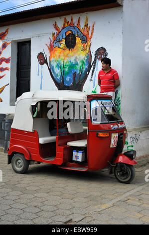 taxi driver leaning against a house wall in front of his three-wheeled vehicle waiting for customers, Guatemala, - Stock Photo
