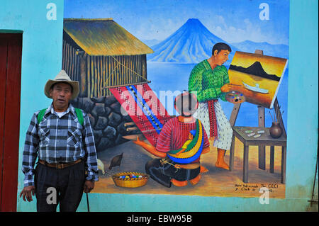 man standing in front of a painting on a house wall showing a man painting a picture and a woman weaving a carpet, - Stock Photo