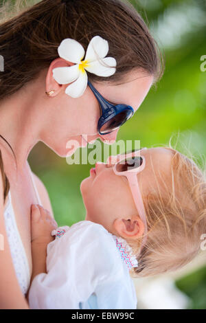 mother and daughter with sunglasses looking at each other, portrait - Stock Photo