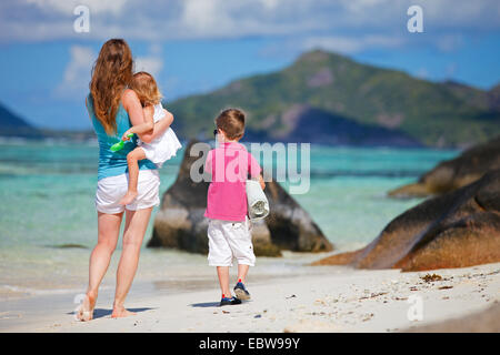 a young mother walking with her two little children on sandy beach - Stock Photo