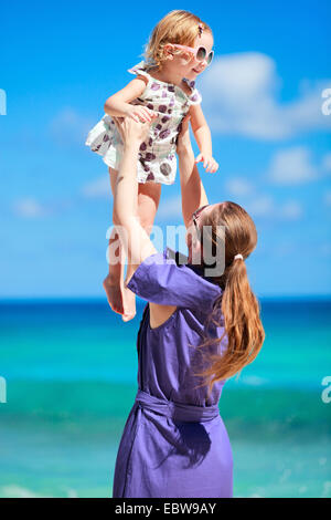 a young mother lifting up her little daughter on tropical beach - Stock Photo