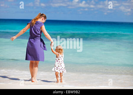 a young mother standing with her little daughter on the beach - Stock Photo