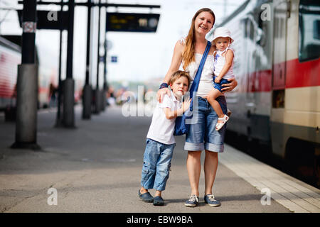 a young mother with her two children waiting for train - Stock Photo