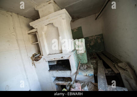 big stove with bedspace in old wooden cottage in abandoned Stechanka village, Chernobyl Exclusion Zone, Ukraine - Stock Photo