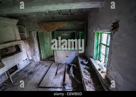 kitchen in old wooden cottage in abandoned Stechanka village, Chernobyl Exclusion Zone, Ukraine - Stock Photo