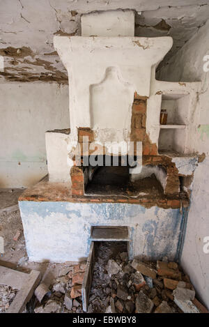big stove in old wooden cottage in abandoned Stechanka village, Chernobyl Exclusion Zone, Ukraine - Stock Photo
