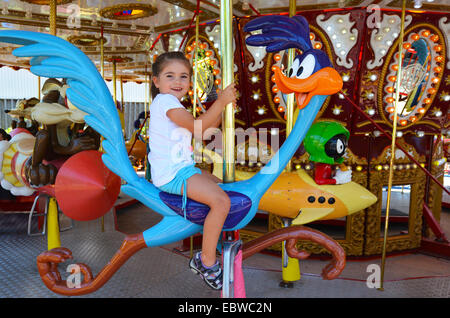 Happy little girl (age 04) ride on carousel in amusement park. - Stock Photo