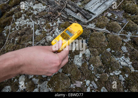 tourist checking radiation level in junk yard near Illinci (or Ilintsy) village in Chernobyl Exclusion Zone, Ukraine - Stock Photo