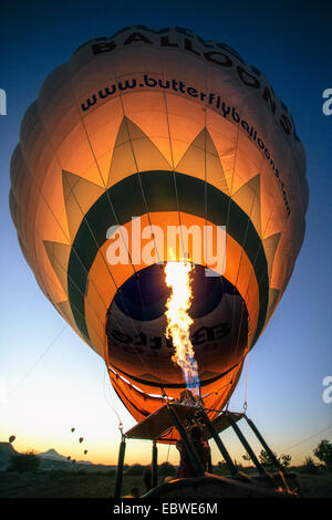 Filling up hot air balloon at sunrise in Cappadocia,Turkey - Stock Photo