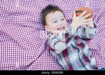 Cute Young Mixed Race Boy Playing With Football Outside On Picnic Blanket. - Stock Photo