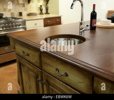 Distressed kitchen cabinets, wooden countertop with modern stainless steel faucet and sink. - Stock Photo