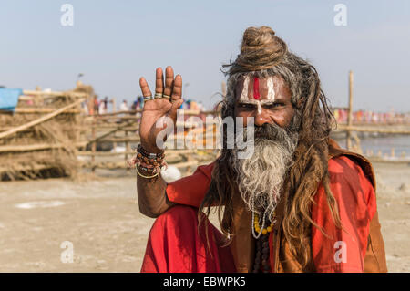 Shiva sadhu, holy man, sitting at the Sangam, the confluence of the rivers Ganges, Yamuna and Saraswati - Stock Photo