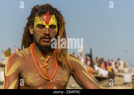 Shiva sadhu, holy man, meditating at the Sangam, the confluence of the rivers Ganges, Yamuna and Saraswati - Stock Photo