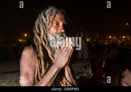 Shiva sadhu, holy man, sitting and praying at night at the Sangam, the confluence of the rivers Ganges, Yamuna and - Stock Photo