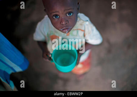 little boy with plastic cup looking up with eyes open wide to the camera, Burundi, Bujumbura - Stock Photo