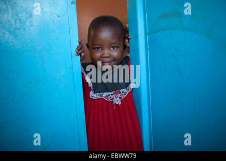 little girl in a red cloth looking out of a blue door, Burundi, Bujumbura Mairie, Bujumbura - Stock Photo