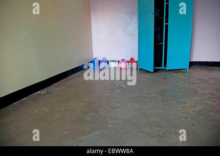 row of plastic potties in the corner of an empty room in an orphanage, Burundi, Bujumbura Mairie, Bujumbura - Stock Photo