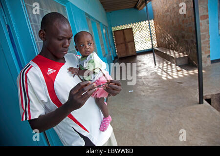 young man with a baby on his arm is standing in a corridor thoughtfully looking at his glasses, Burundi, Bujumbura - Stock Photo