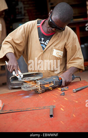 teenager working with angle grinder in a workshop of an aid organisation, Burundi, Ngozi - Stock Photo