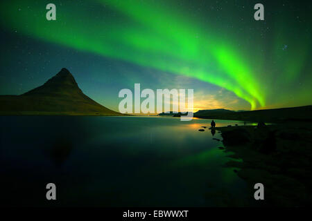 Kirkjufel by night , whit aurora borealis in the sky and siluette of a person. - Stock Photo