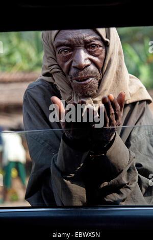elderly man begging at open window of a car, Burundi, Bujumbura Rural, Bugarama - Stock Photo