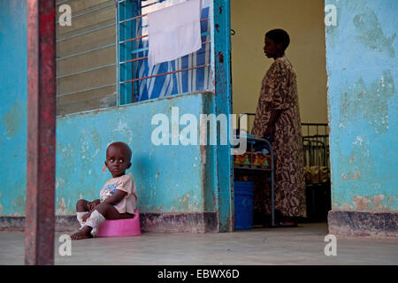 little boy sitting on a potty in front of an orphanage, woman inside is making beds, Burundi, Bujumbura Marie, Bujumbura - Stock Photo