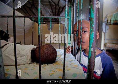 boy sitting beside a bed in which a little girl is sleeping, Burundi, Bujumbura Marie, Bujumbura - Stock Photo