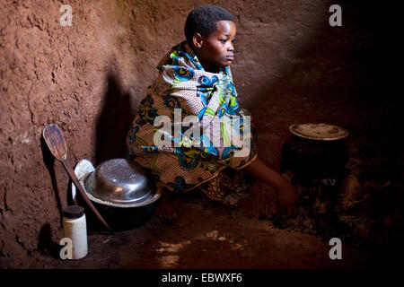 woman in traditional clothes preparing a meal on the kitchen floor of a humble mud house, Burundi, Karuzi, Buhiga - Stock Photo