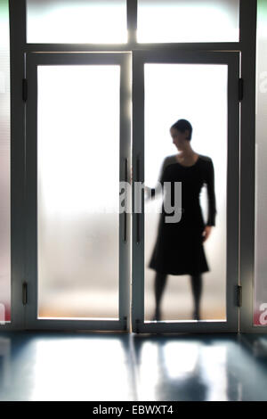 view through a glass door at the silhouette of a young woman who is opening one of the two door wings - Stock Photo