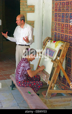 young woman sitting at work in a carpet workshop with an older man standing beside her talking and gesticulating, - Stock Photo