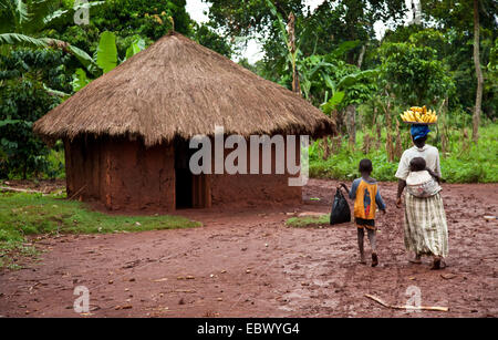 mother transporting bananas to the local market with her kids and passes a mud house, Uganda, Jinja - Stock Photo