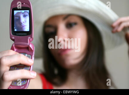 young woman taking self photograph with mobile phone - Stock Photo
