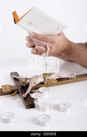 bible in the hand of a man, christian things on a desk - Stock Photo