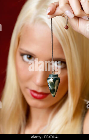 blond young woman holding a pendulum in her hands for reading the future - Stock Photo