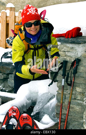 woman on a winter hike at a frozen water tap, France - Stock Photo